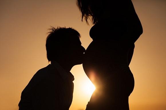 Homme qui embrasse le ventre de sa femme