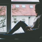 femme triste regardant par la fenêtre