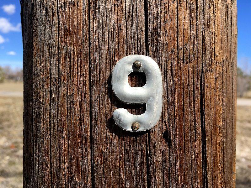 chiffre neuf métallique sur un support bois